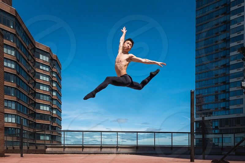 Male dancer in movement leaping through the air photo