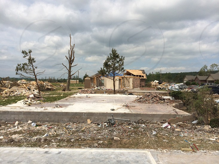 wrecked houses with trees under white cloudy sky during daytime photo