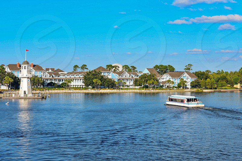 Orlando Florida. February 09 2019. Taxi boat sailing on lake with background of villas and lighthouse at Lake Buena Vista area (2) photo