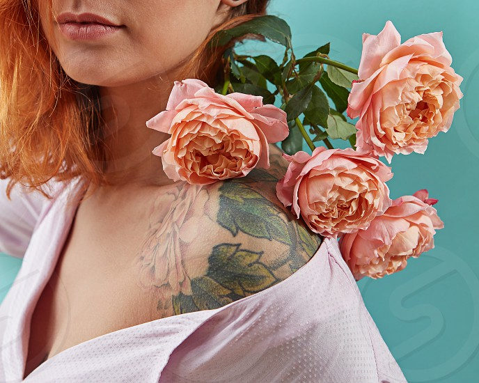Beautiful redhead woman with living coral colored flowers on her shoulders with tattoo roses on a blue background. Greeting holiday card for Mother's or Woman's Day. photo