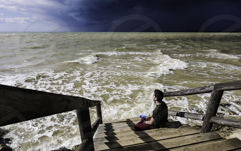 Young man sitting on his back facing the rough sea photo