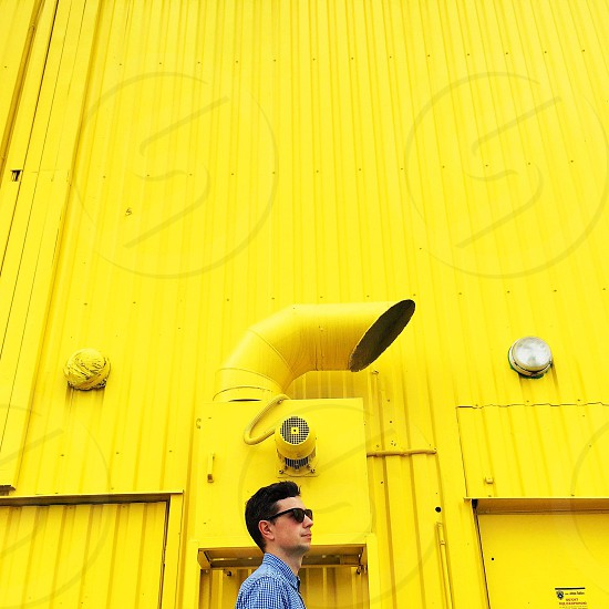 man wearing blue formal shirt and black sunglasses standing beside yellow painted building during daytime photo