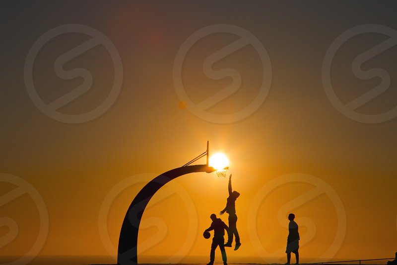 Silhouette basketball at sunset photo
