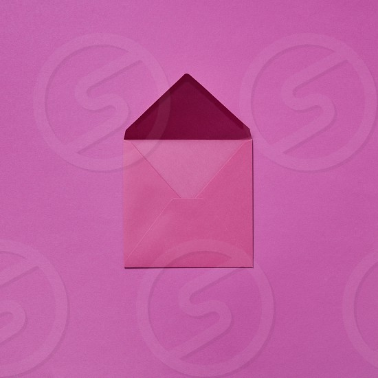 Mock up handcraft open envelope for congratulation post card on a magenta background with copy space. Flat lay photo