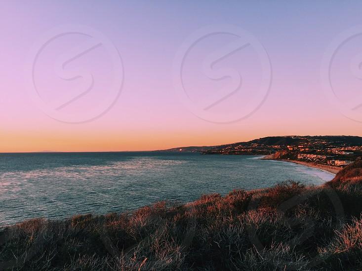 blue purple orange sky above dark blue body of water bordered by  green gray brown grassy low cliffs photo