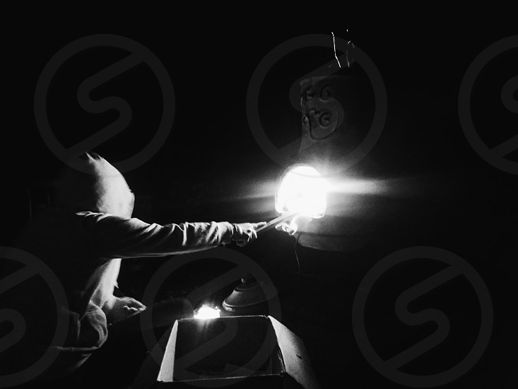 person with hoodie holding light in dark room photo