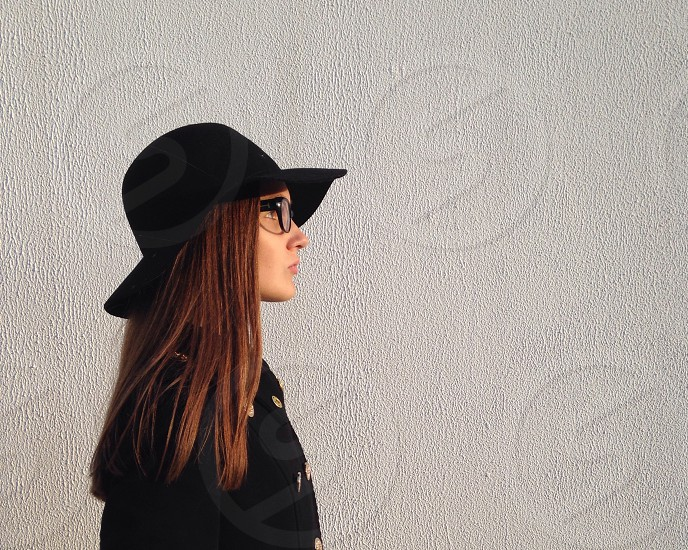 woman in black coat and black summer hat standing sideways against the wall photo
