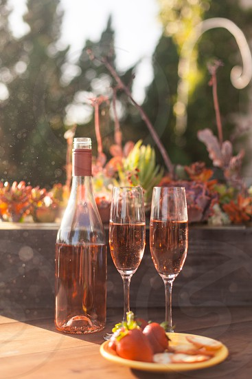 two champagne flutes filled with rose wine on a table next to the bottle and a plate of strawberries and crackers photo