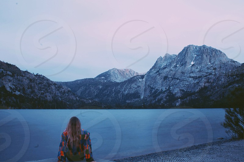 woman sitting in front of lake photo