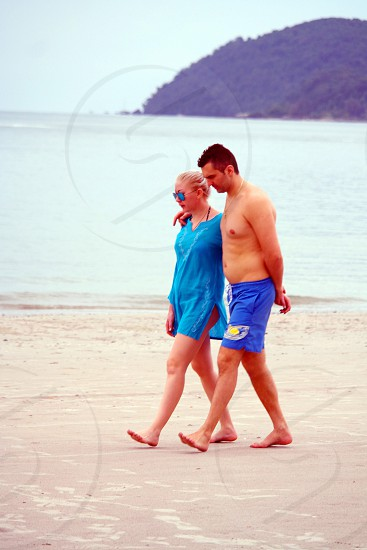 man in blue board shorts walking with woman in blue split neck side slit shirt on seashore during fine weather photo