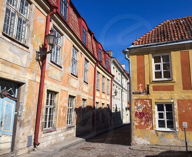 Outdoor day horizontal colour colourful vivid vibrant bright contrast orange yellow pink peach red blue Sky buildings architecture alley alleyway road cobble cobblestone Tallinn Estonia medieval traditional culture Europe European travel tourist tourism photo