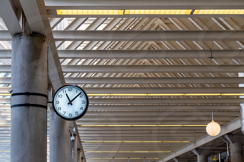 Round clock at the railway station or at the airport under the roof of metal structures for passengers looking time. photo