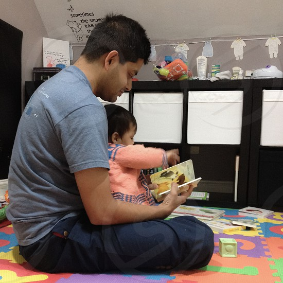 Baby reading on father's lap photo