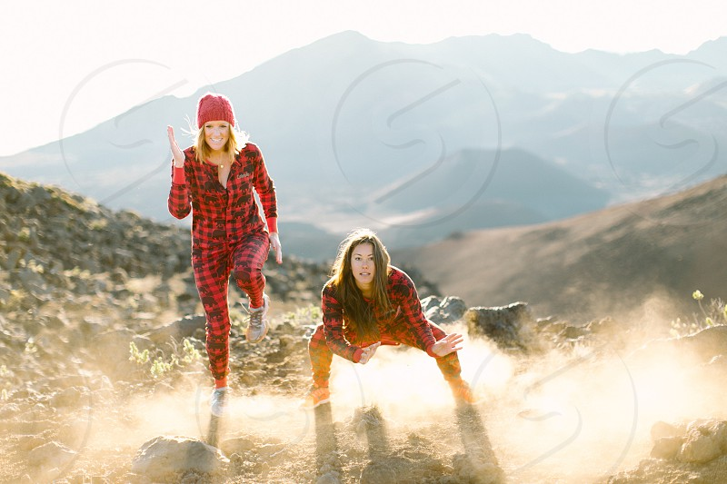 2 womens wearing red and black plaid  onesie on rocky mountain photo
