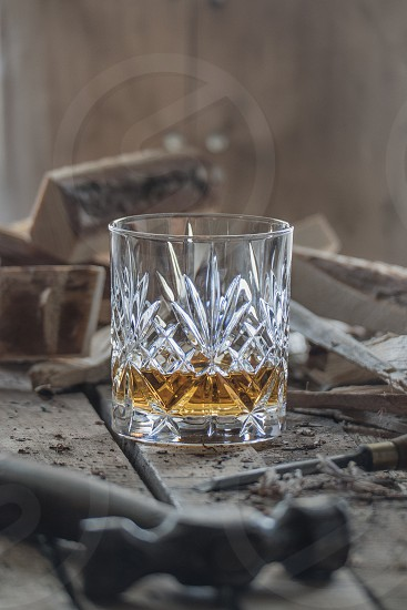 scotch whisky in a glass surrounded by wood wood cuttings and old cooperage tools photo