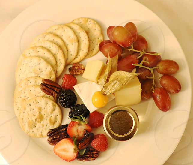 Cheese fruit nuts crackers berries photo