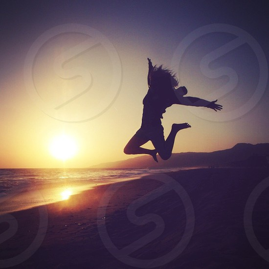 woman jumping silhouette with sunset view photo