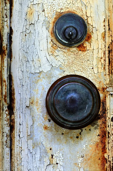 Door knob with flaking paint and rust offers nice texture. photo