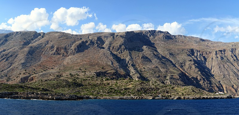 panoramic image of Crete (Greece) mountains of Libyan Sea side. driving with a boat along from Samaria gorge towards Loutro village. made of 4 images. photo