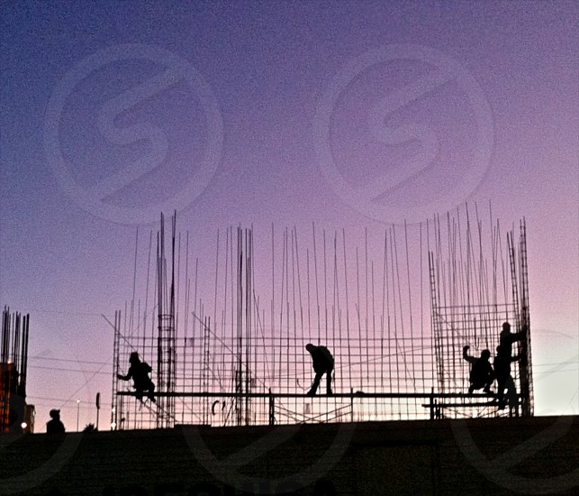 people working on construction site at sunrise photo