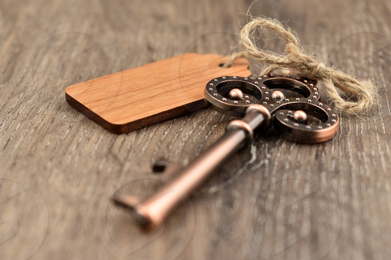 Decorative metal key on a wooden background. Decorated key images. Romantic key with wooden label. Key on the table photo