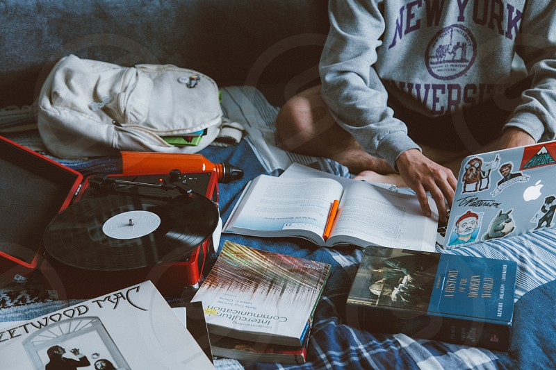 person in gray long sleeved shirt in front of white books and black red turn table on bed photo