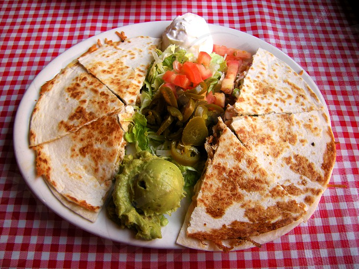Quesadillas with guacamole sour cream peppers pico de gallo white plate on red checkered tablecloth photo