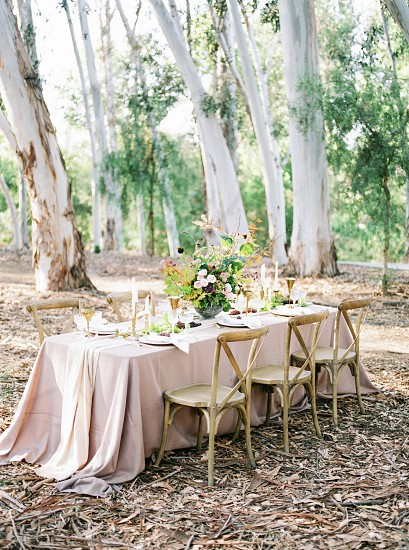 A fall-styled wedding table with linens plates and flowers. photo