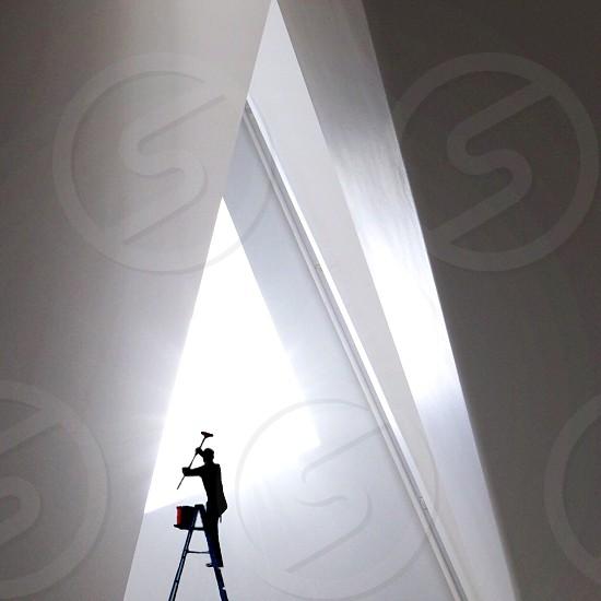man on ladder painting photo