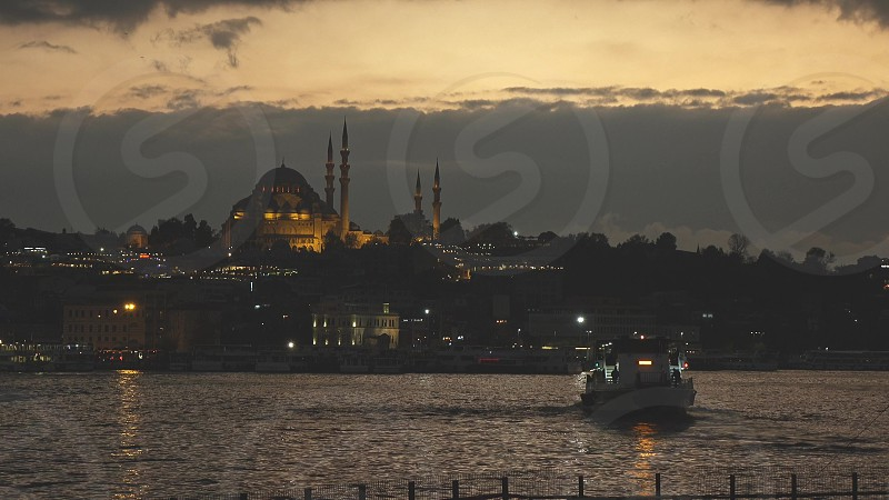Looking over Golden Horn to Suleymaniye Mosque on a twilight dramatic sky. Historical old town Istanbul in prayer time. 4K UHD video 3840 2160p. photo
