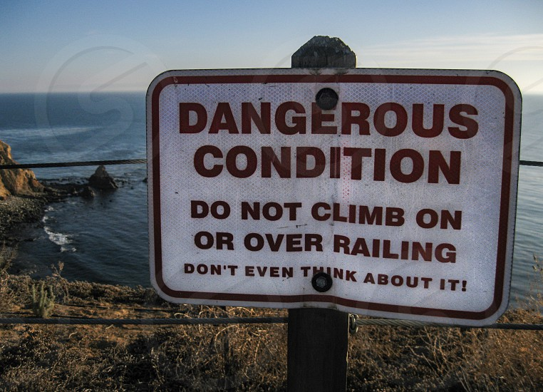 Warning sign at a steep cliff edge on the Palos Verdes Peninsula near Los Angeles overlooking the Pacific Ocean has a slightly humorous tone. photo
