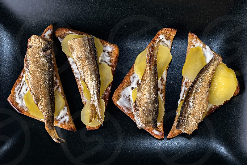 Sandwiches with smoked sprats on black plate. Above view photo