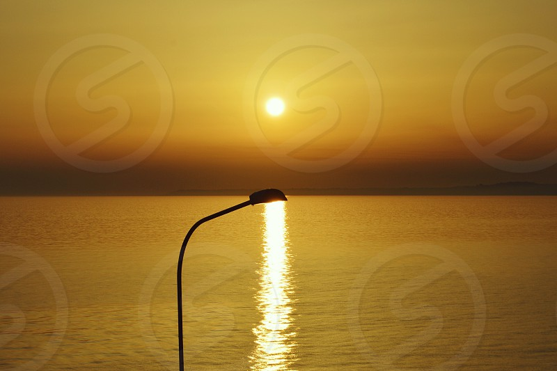 photo of street light with sea background during golden hour photo