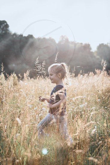 Little happy girl walking through a tall grass in the countryside. Candid people real moments authentic situations photo