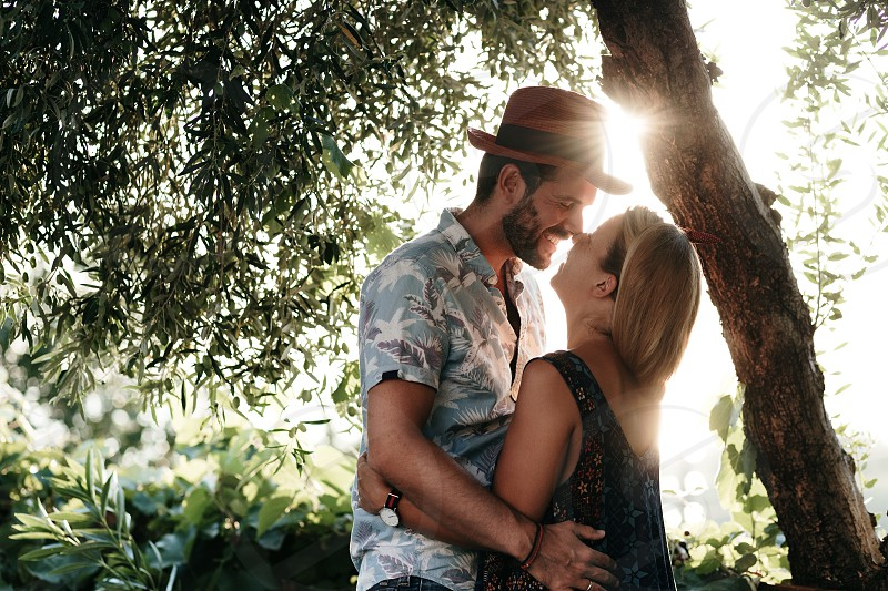 Couple in love kissing in a garden in sunset photo