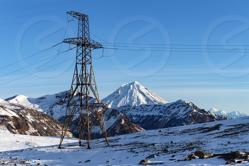 High voltage metal tower in highlands on sunny winter weather. View on high voltage power line on background of snow-capped cone of Vilyuchinsky Volcano. Eurasia Russian Far East Kamchatka Peninsula photo