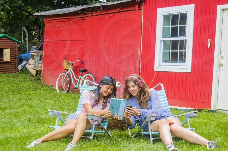 2 smiling girls on loungers in green grass lawn in front of red cabin photo