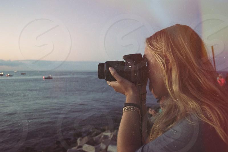 woman holding camera capturing ocean photo