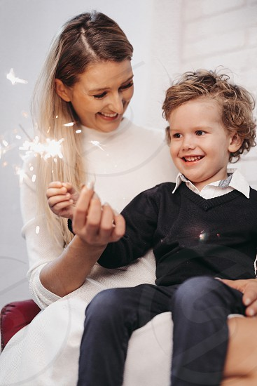 Mother and sun sitting on a chair and firing sparklers in Christmas decorated studio photo