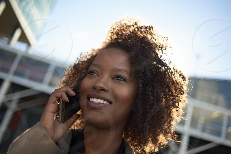 Young black business woman talking on her mobile phone outside in the city on a beautiful sunny day in spring photo