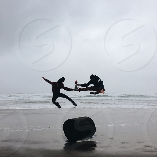 2 people doing karate kick over wood log on beach photo
