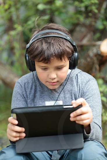 Teenager boy in headphones using tablet PC. He listening to music or watching movie photo