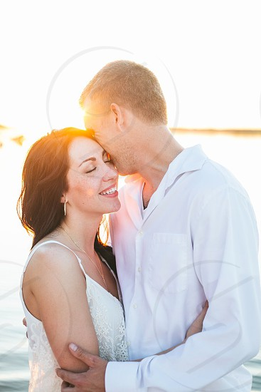 By the lake lake sunset sun warm love embrace cuddle smile happy happy couple white golden sunset smile engagement engaged couple wedding river warmth happiness Sun flare   photo