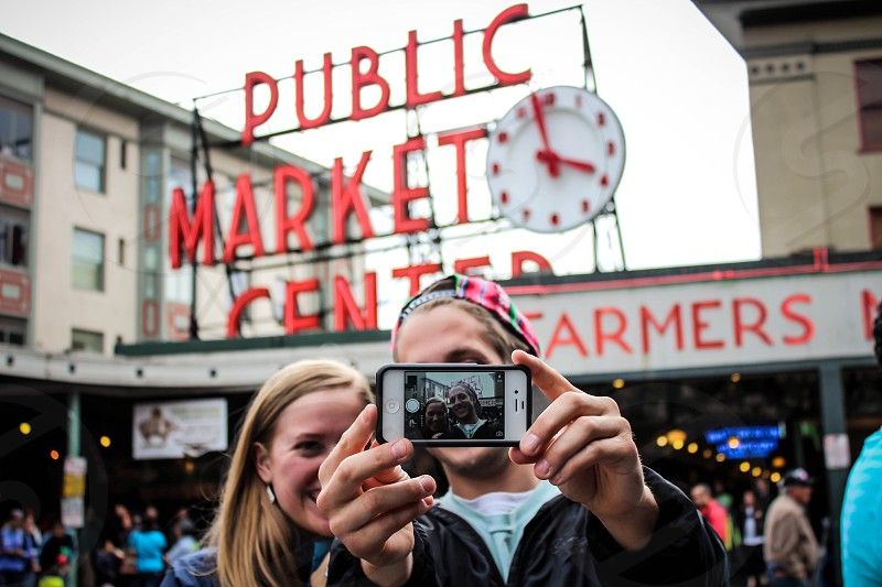 man and woman taking selfie in front of public market center photo