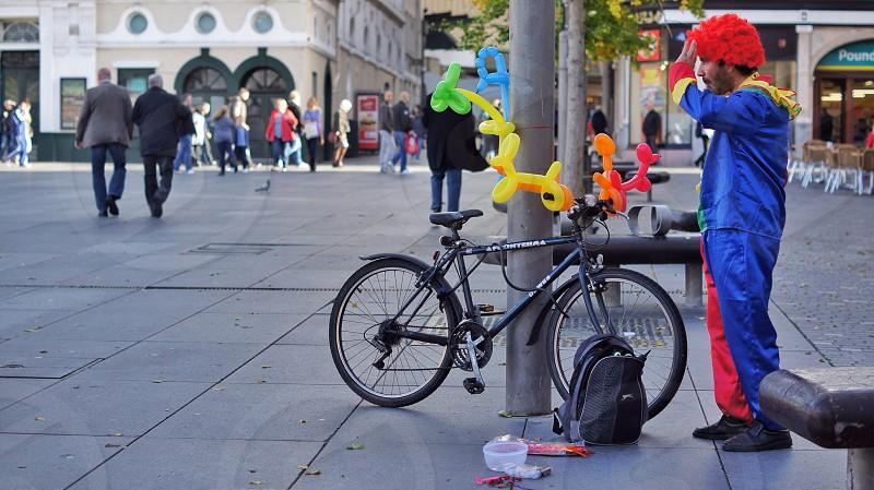 clown standing beside black framed mountain bike photo