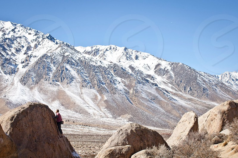 person in black pants climbing on brown rock below snow covered mountains under blue sunny sky photo