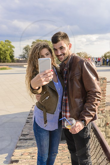 Long haired young woman enjoying the time by taking selfie with her handsome boyfriend photo