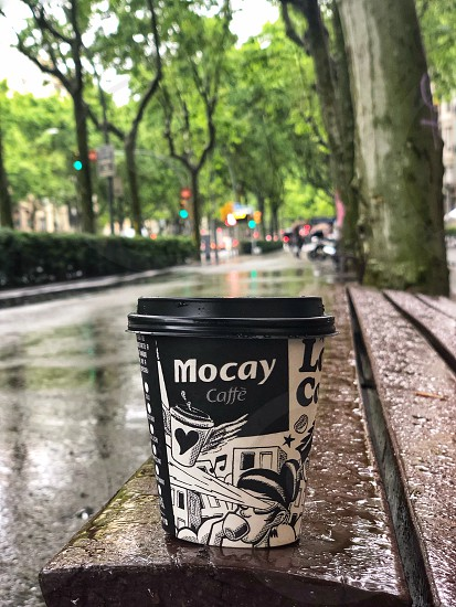 There is nothing better on a cool rainy day than a cup of hot aromatic coffee.  Disposable paper cup of coffee on the wet bench of the city alley. Barcelona  photo