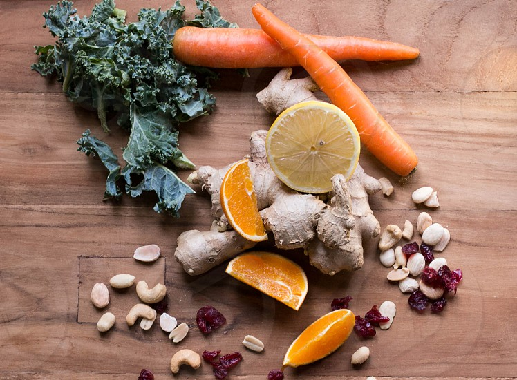 ginger kale carrots cranberries lemon orange and nuts on a wooden surface photo