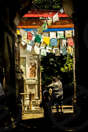 man and child standing under yellow white blue and green bunting during daytime photo